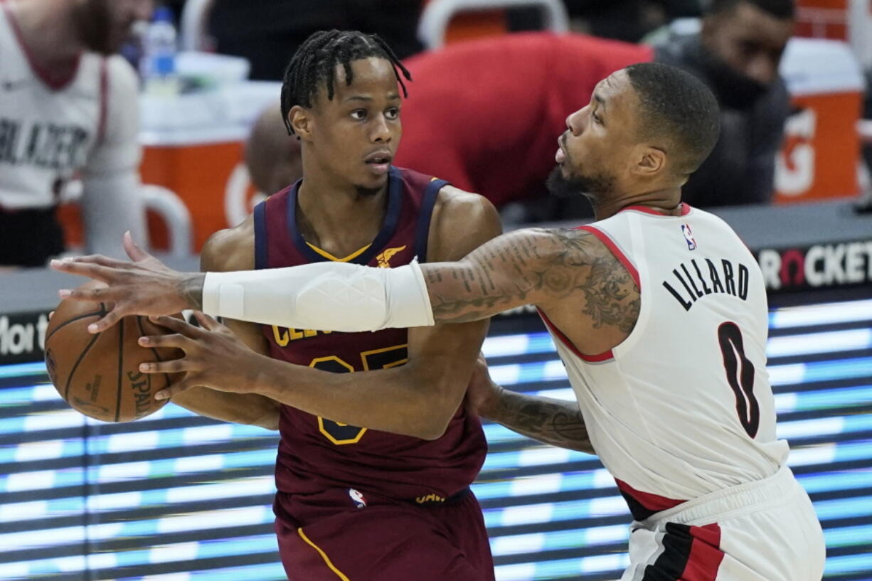 Portland Trail Blazers' Damian Lillard (0) defends against Cleveland Cavaliers' Isaac Okoro during the second half of an NBA basketball game Wednesday, May 5, 2021, in Cleveland.