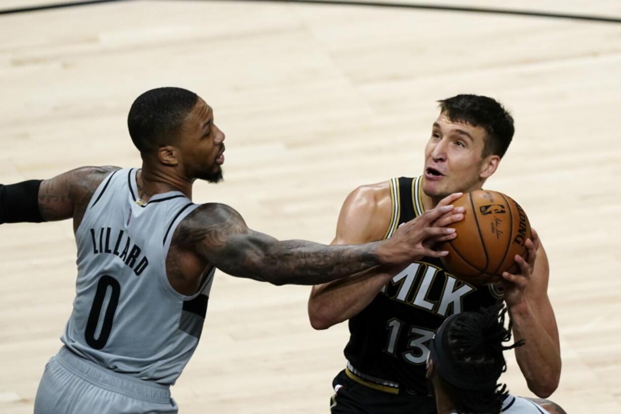Atlanta Hawks guard Bogdan Bogdanovic (13) is defended by Portland Trail Blazers guard Damian Lillard (0) as he tries to shoot in the first half of an NBA basketball game Monday, May 3, 2021, in Atlanta.