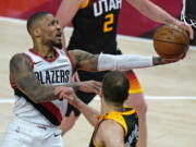 Portland Trail Blazers guard Damian Lillard, left, lays the ball up as Utah Jazz forward Bojan Bogdanovic, right, watches during the second half of an NBA basketball game Wednesday, May 12, 2021, in Salt Lake City.