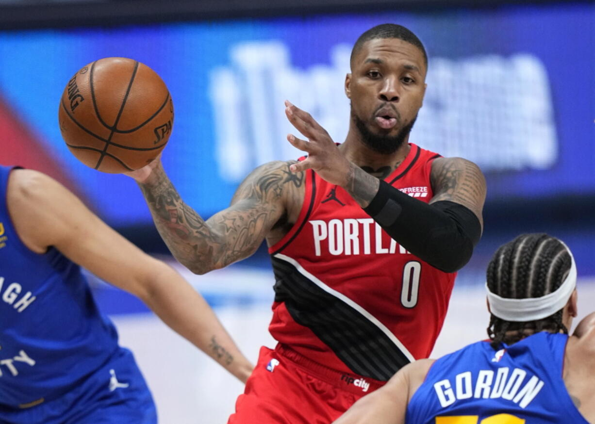 Portland Trail Blazers guard Damian Lillard (0) passes the ball against the Denver Nuggets during the second half of Game 1 of a first-round NBA basketball playoff series Saturday, May 22, 2021, in Denver.