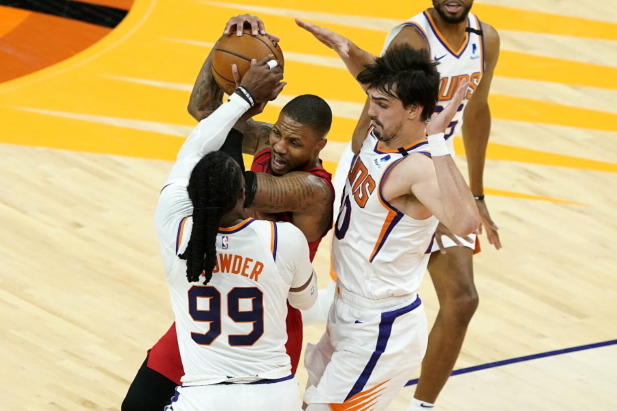 Portland Trail Blazers guard Damian Lillard is pressured by Phoenix Suns forward Jae Crowder (99) and forward Dario Saric, right, during the second half of an NBA basketball game, Thursday, May 13, 2021, in Phoenix.