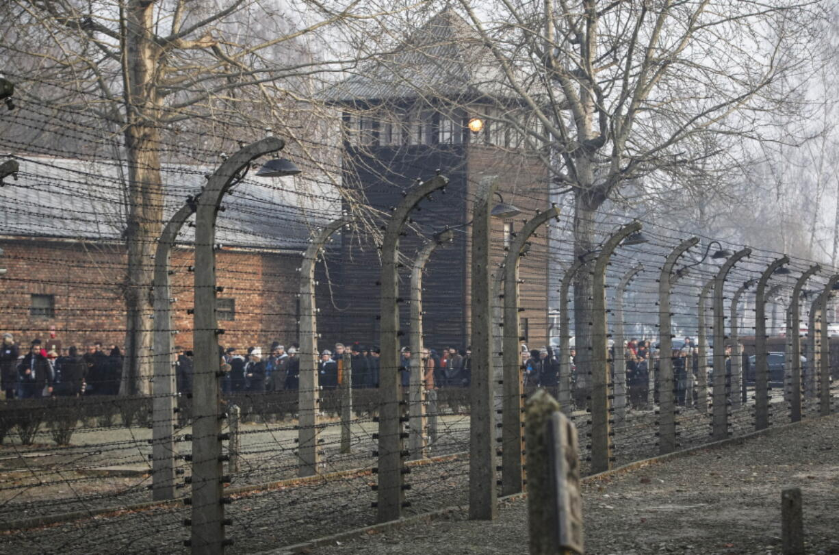 """FILE- In this file photo taken Jan. 27, 2020, people are seen arriving at the site of the Auschwitz-Birkenau Nazi German death camp, where more than 1.1 million were murdered, in Oswiecim, Poland, for observances marking 75 years since the camp's liberation by the Soviet army. Needham, Massachusetts-based TripAdvisor on Thursday, May 6, 2021, faced criticism from the camp's museum and memorial after an author posted an inappropriate review of the museum on the TripAdvisor website, stating the reviewer visited to """"test the chamber"""". The company originally declined to remove the message."""