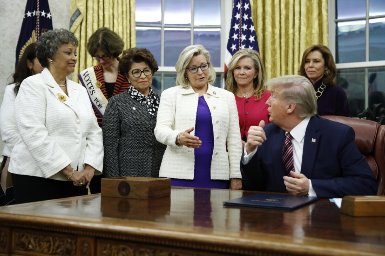 FILE - In this Nov. 25, 2019, file photo, Rep. Liz Cheney, R-Wyo., center, speaks with President Donald Trump during a bill signing ceremony for the Women's Suffrage Centennial Commemorative Coin Act in the Oval Office of the White House in Washington.