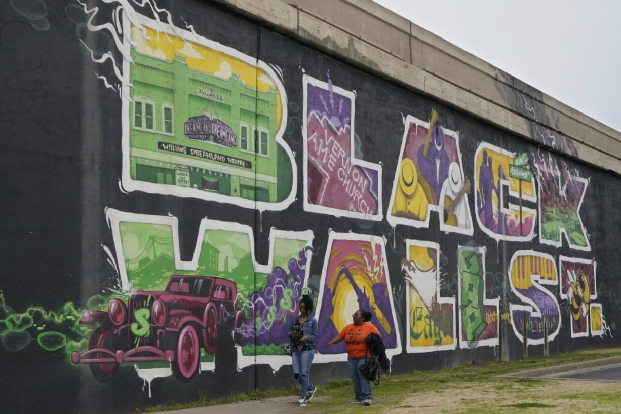 Javohn Perry, left, of Seattle, and her cousin, Danielle Johnson, right, of Beggs, Okla., walk past the Black Wall Street mural Monday, April 12, 2021, in Tulsa, Okla. The original Black Wall Street vaporized a hundred years ago, when a murderous white mob laid waste to what was the nation's most prosperous Black-owned business district and residential neighborhood.