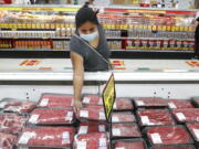 FILE - In this April 29, 2020 file photo, a shopper wears a mask as she looks over meat products at a grocery store in Dallas.   Wholesale prices rose a higher-than-expected 0.6% in April, driven by a sharp rise in food costs.