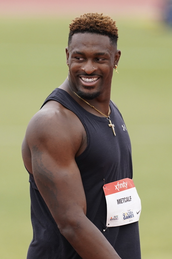 Seattle Seahawks wide receiver DK Metcalf smiles after competing in the second heat of the men's 100-meter dash prelim during the USATF Golden Games at Mt. San Antonio College Sunday, May 9, 2021, in Walnut, Calif.