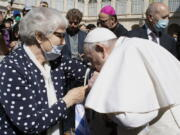 Pope Francis leans and kiss a tattoo on the arm of Holocaust survivor Lidia Maksymowicz, a Polish citizen who was deported to Auschwitz from her native Belarus, during his weekly general audience at the Vatican, Wednesday, May 26, 2021. Pope Francis has kissed the tattoo of an Auschwitz survivor during a general audience on Wednesday. Lidia Maksymowicz, a Polish citizen who was deported to Auschwitz from her native Belarus, showed the pope the number tattooed on her arm by the Nazis, and Francis leaned over and kissed it Wednesday. Maksymowicz told Vatican News that she did not exchange words with the pope.