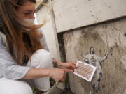 Artist Alessia Babrow holds the Vatican stamps next to her street art May 14 at the Vatican.