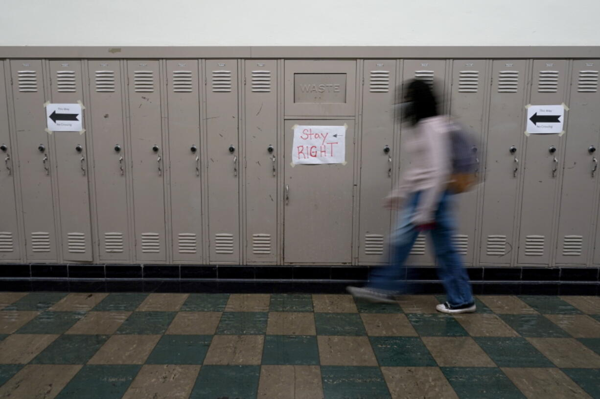 A student walks between classes at Wyandotte High School in Kansas City, Kan., on the first day of in-person learning Wednesday, March 30, 2021. The school, like other schools nationwide, has made extra efforts to keep kids at risk of dropping out engaged as classes went virtual due to the pandemic.