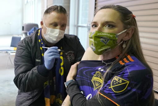 FILE - In this May 2, 2021, file photo, Stephanie Birman, right, a Seattle Sounders season ticket holder, wears a Sounders mask, jersey and earrings as she gets the Johnson & Johnson COVID-19 vaccine at a clinic in a concourse at Lumen Field prior to an MLS soccer match between the Sounders and the Los Angeles Galaxy. On Thursday, May 20, 2021, authorities in King County, Wash., which includes Seattle, said all people should continue wearing masks indoors until 70% of people in the county 16 and older are fully vaccinated. (AP Photo/Ted S.