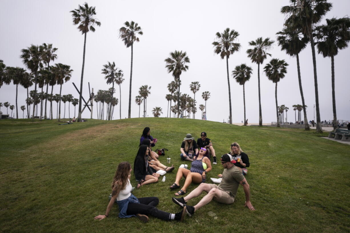 FILE - In this May 5, 2021, file photo, a group of friends, who said they are fully vaccinated for COVID-19, mingle on the beach in the Venice section of Los Angeles. COVID-19 deaths in the U.S. have tumbled to an average of just over 600 per day - the lowest level in 10 months - with the number of lives lost dropping to single digits in well over half the states and hitting zero on some days. (AP Photo/Jae C.