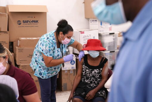 FILE - In this April 10, 2021, file photo, registered nurse Ashleigh Velasco, left, administers the Johnson & Johnson COVID-19 vaccine to Rosemene Lordeus, right, at a clinic held by Healthcare Network in Immokalee, Fla. Fewer Americans are reluctant to get a COVID-19 vaccine than just a few months ago, but questions about side effects and how the shots were tested still hold some back, according to a new poll that highlights the challenges at a pivotal moment in the U.S. vaccination campaign.