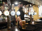 A member of staff serves a drink, as pubs, cafes and restaurants in England reopen indoors under the latest easing of the coronavirus lockdown, in Manchester, England, Monday, May 17, 2021. Pubs and restaurants across much of the U.K. are opening for indoor service for the first time since early January even as the prime minister urged people to be cautious amid the spread of a more contagious COVID-19 variant.