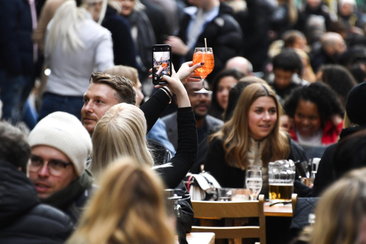 FILE - In this Monday, April 12, 2021 file photo, a woman takes a photo on her phone of her drink in Soho, London, as some of England's coronavirus lockdown restrictions were eased by the government. Thanks to an efficient vaccine roll out program and high uptake rates, Britain is finally saying goodbye to months of tough lockdown restrictions. From Monday May 17, 2021, all restaurants and bars can fully reopen, as can hotels, cinemas, theatres and museums, and for the first time since March 2020, Britons can hug friends and family and meet up inside other people's houses.