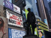 A statue of playwright and performer George M. Cohan stands in New York's Times Square in front of billboards for Broadway shows May 6.