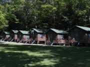FILE - This Thursday, June 4, 2020 file photo shows a row of cabins at a summer camp in Fayette, Maine. On Friday, May 28, 2021, the Centers for Disease Control and Prevention posted guidance saying kids at summer camps can skip wearing masks outdoors, with some exceptions. Children who aren't fully vaccinated should still wear masks outside when they're in crowds or in sustained close contact with others - and when they are inside, and fully vaccinated kids need not wear masks indoors or outside, the CDC says. (AP Photo/Robert F.