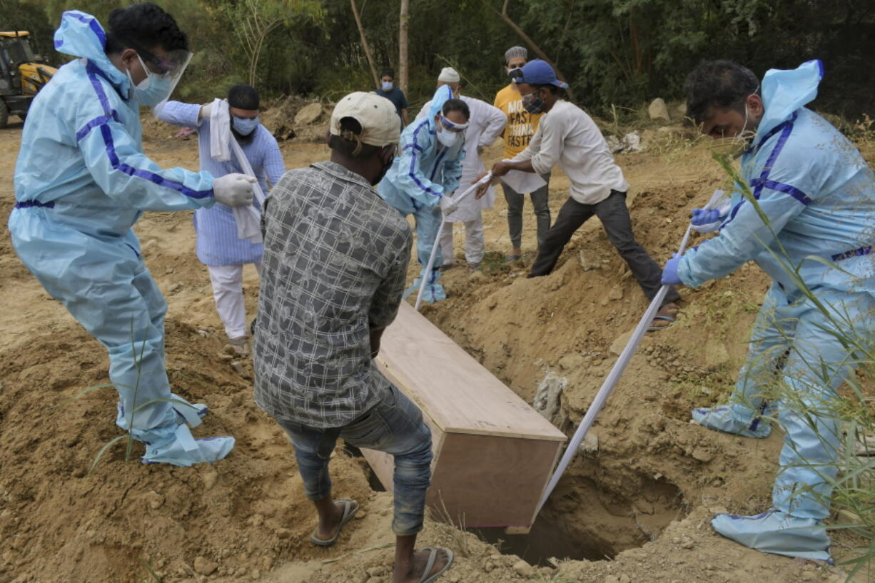 Relatives bury the body of a COVID-19 victim at a graveyard in New Delhi, India, Tuesday, May 4, 2021. India's official count of coronavirus cases surpassed 20 million Tuesday, nearly doubling in the past three months, while deaths officially have passed 220,000. Staggering as those numbers are, the true figures are believed to be far higher, the undercount an apparent reflection of the troubles in the health care system.
