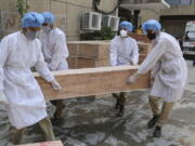 Jammu and Kashmir State Disaster Response Force soldiers carry empty coffins for transporting bodies of people who died of COVID-19 outside government medical hospital in Jammu, India, Wednesday, May 19, 2021.
