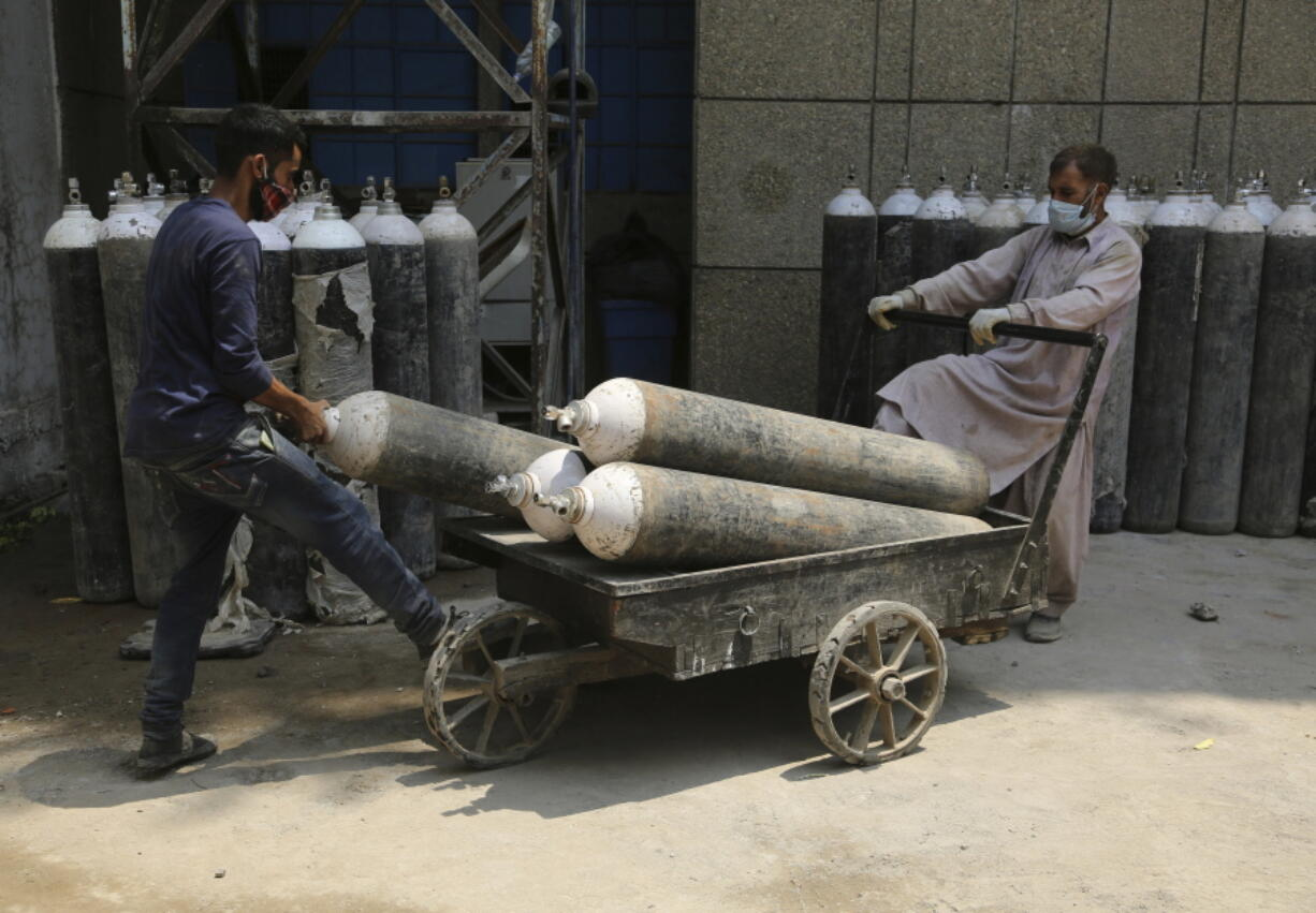 Workers load oxygen cylinders onto a hand cart to be carried inside the COVID-19 wards at a government run hospital in Jammu, India, Friday, May 7, 2021. With coronavirus cases surging to record levels, Indian Prime Minister Narendra Modi is facing growing pressure to impose a harsh nationwide lockdown amid a debate whether restrictions imposed by individual states are enough.