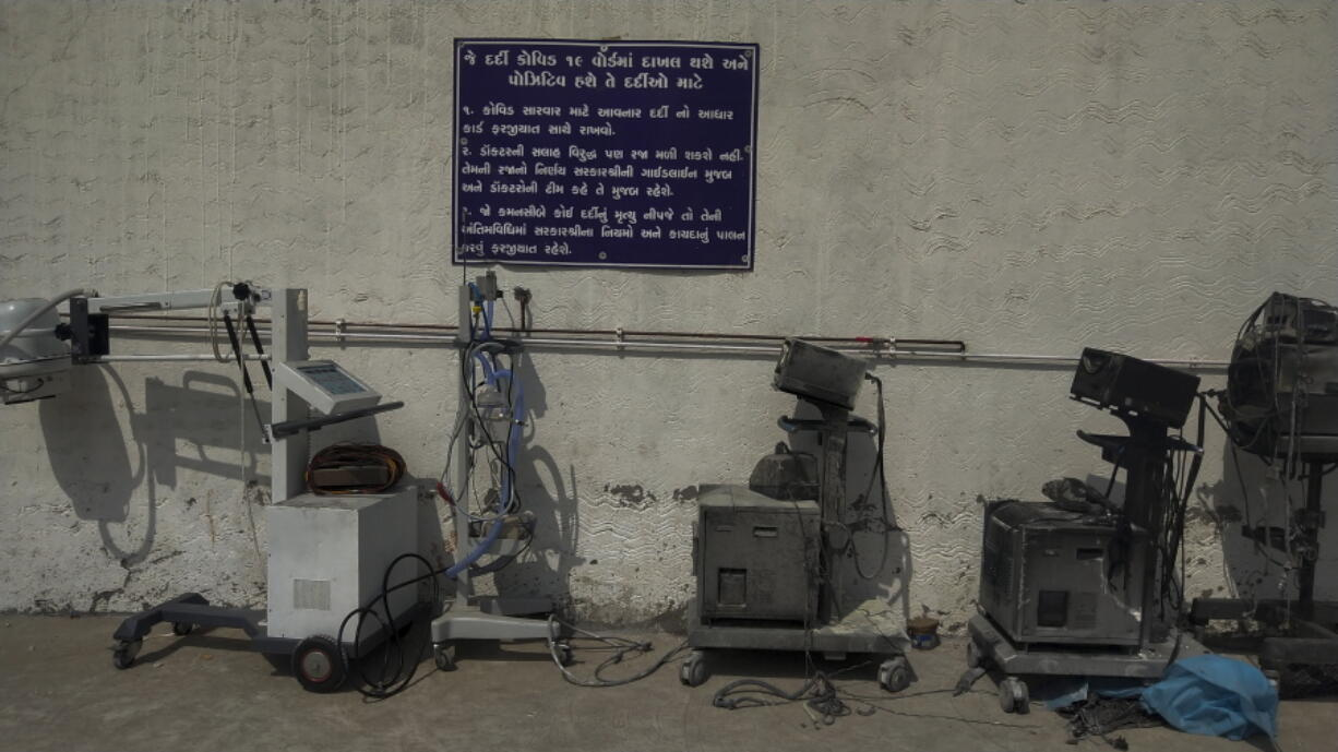 Instructions for COVID-19 patients are seen on a signage in Gujarati next to damaged equipments after a deadly fire at the Welfare Hospital in Bharuch, western India, Saturday, May 1, 2021. The fire in a COVID-19 ward of the hospital killed multiple patients early Saturday, as the country grappling with the worst outbreak yet steps up a vaccination drive for all its adults even though some states say don't have enough jabs.