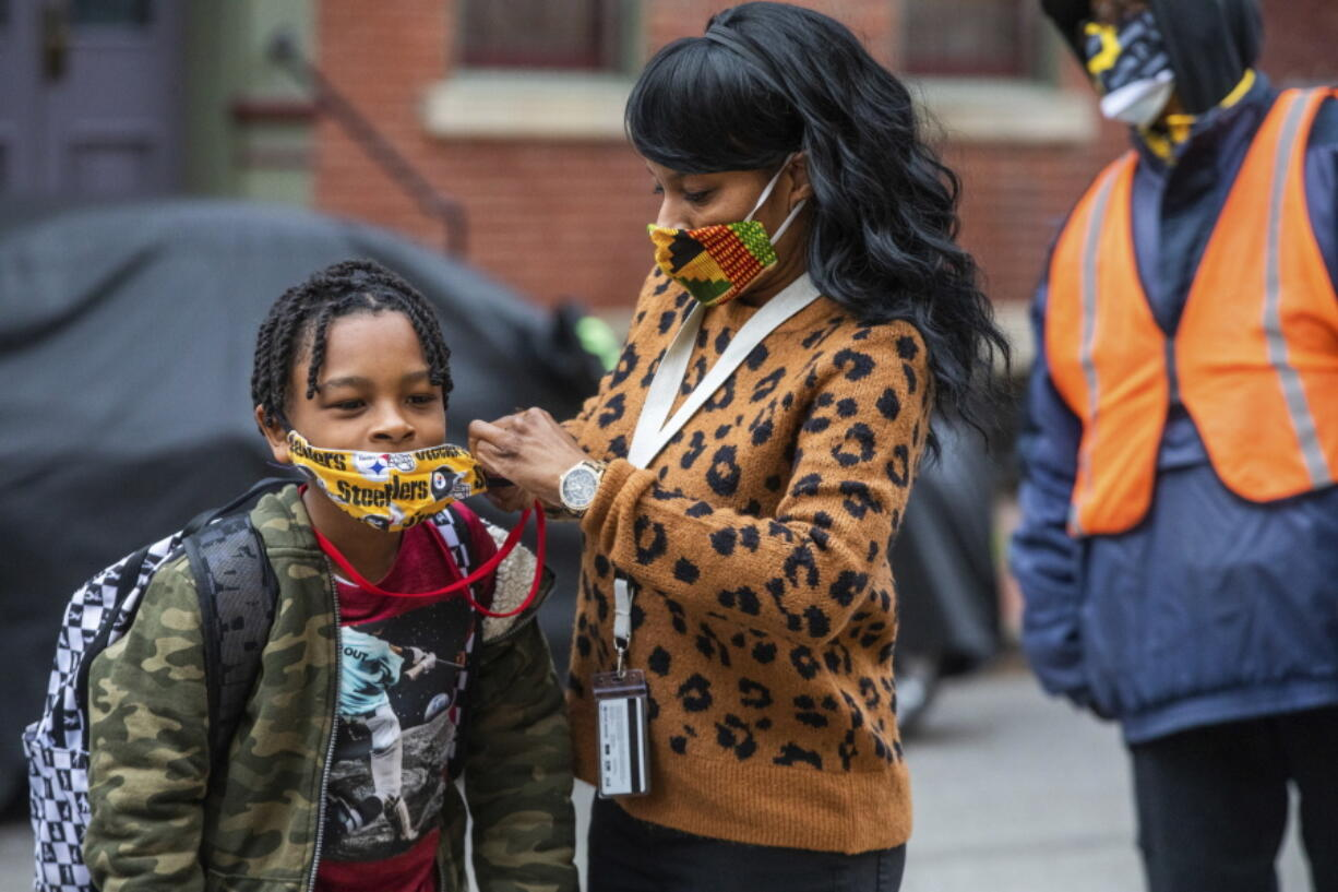 FILE - In this Monday, March 29, 2021, file photo, Jenea Edwards, of the North Side, helps her son Elijah, 9, in the third grade, with his mask before heading into Manchester Academic Charter School on the first day of in-person learning via a hybrid schedule, in Pittsburgh. Dozens of school districts around the country have eliminated requirements for students to wear masks, and many more are likely to ditch mask requirements before the next academic year.