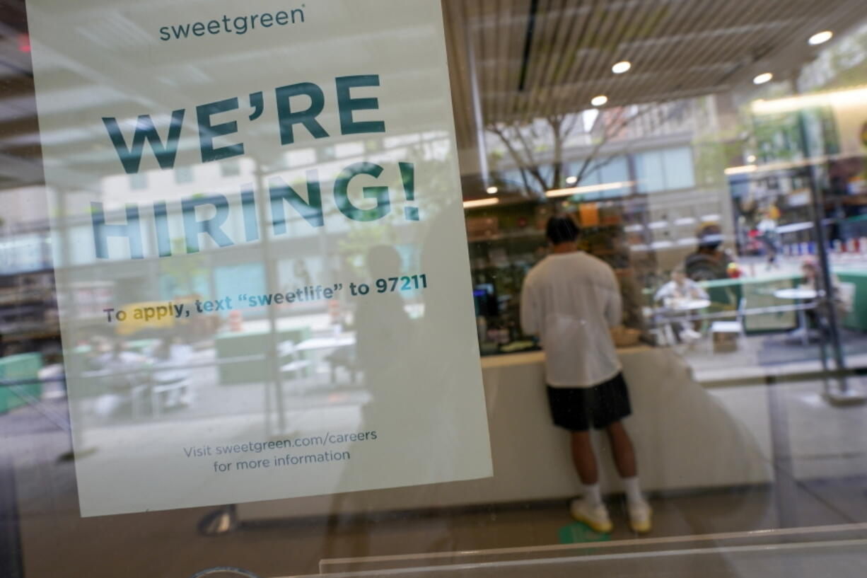 A signs announcing they are hiring hangs in the window of a restaurant in the Greenwich Village neighborhood of Manhattan in New York, Tuesday, May 4, 2021. Some restaurants in New York City are starting to hire employees now that they can increase their indoor dining to 75% of capacity starting May 7.