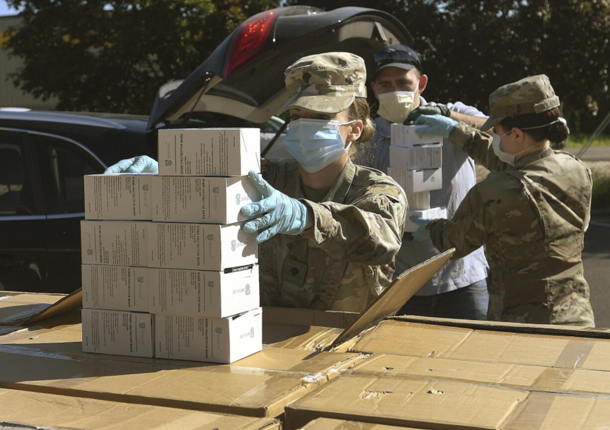 FILE - In this Wednesday, May 27, 2020, file photo, Oregon National Guard's Ashley Smallwood, of Springfield, Ore., counts out boxes of face masks to be given to Willamette Valley farmers while participating in a distribution event at the Oregon State University Extension Service-Linn County office in Tangent, Ore. Oregon adopted a controversial rule on Tuesday, May 4, 2021 that indefinitely extends coronavirus mask and social distancing requirements in all businesses in the state.