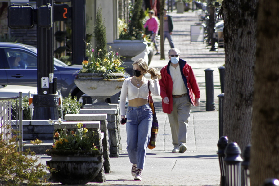FILE - In this April 11, 2021, file photo, residents wearing masks walk in downtown Lake Oswego, Ore.