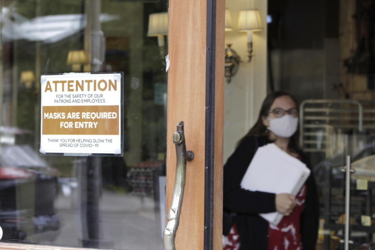 A sign reminds customers to wear their masks at a bakery in Lake Oswego, Ore., on Friday, May 21, 2021. As the federal government and many states ease rules around mask-wearing and business occupancy, some blue states like Oregon and Washington are still holding on to some longtime coronavirus restrictions.