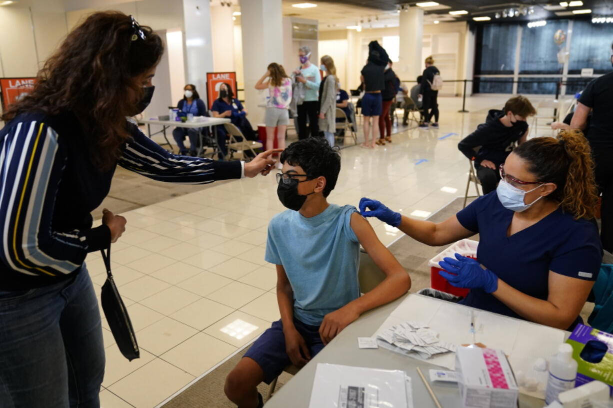 Nouf Albarakati, left, of Narberth Pa., comforts her son Manaf Albarakati, 14, before he receives a Pfizer COVID-19 vaccination from registered nurse Alicia Jimenez at a Montgomery County, Pa. Office of Public Health vaccination clinic at the King of Prussia Mall, Tuesday, May 11, 2021, in King of Prussia, Pa.