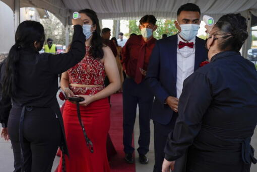 Grace Gardens Event Center employees check temperatures of young people attending prom at the Grace Gardens Event Center in El Paso, Texas on Friday, May 7, 2021. Around 2,000 attended the outdoor event at the private venue after local school districts announced they would not host proms this year. Tickets cost $45.