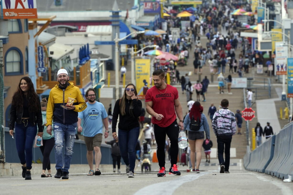 FILE - In this May 13, 2021, file photo, May 13, 2021, visitors walk without masks on the pier in Santa Monica, Calif. A number of states immediately embraced new guidelines from the CDC that say fully vaccinated people no longer need to wear masks indoors or out in most situations. But other states - and some businesses -- are taking a wait-and-see attitude.