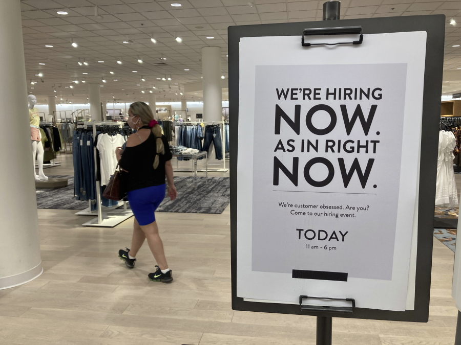 A customer walks behind a sign at a Nordstrom store seeking employees, Friday, May 21, 2021, in Coral Gables, Fla.  The number of Americans seeking unemployment benefits dropped last week to 406,000, a new pandemic low and more evidence that the job market is strengthening as the virus wanes and economy further reopens.