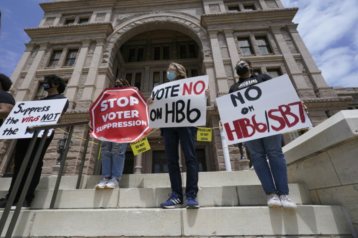 FILE - In this April 21, 2021, file photo, people opposed to Texas voter bills HB6 and SB7 hold signs during a news conference hosted by Texas Rising Action on the steps of the State Capitol in Austin, Texas. Republican lawmakers around the country are pressing ahead with efforts to tighten voting laws, despite growing warnings from business leaders that the measures could harm democracy and the economic climate.