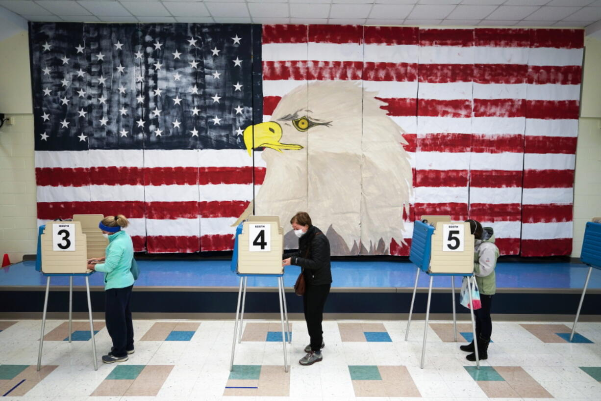FILE - In this Nov. 3, 2020, file photo voters cast their ballots under a giant mural at Robious Elementary school on Election Day, in Midlothian, Va. As Republicans roll back access to the ballot, Democratic lawmakers have been quietly moving to expand voting rights. In Virginia, Maryland, Nevada and other states where Democrats have control, lawmakers are pushing to make it easier to cast ballots by mail, increase early voting and require greater oversight over changes to election law.