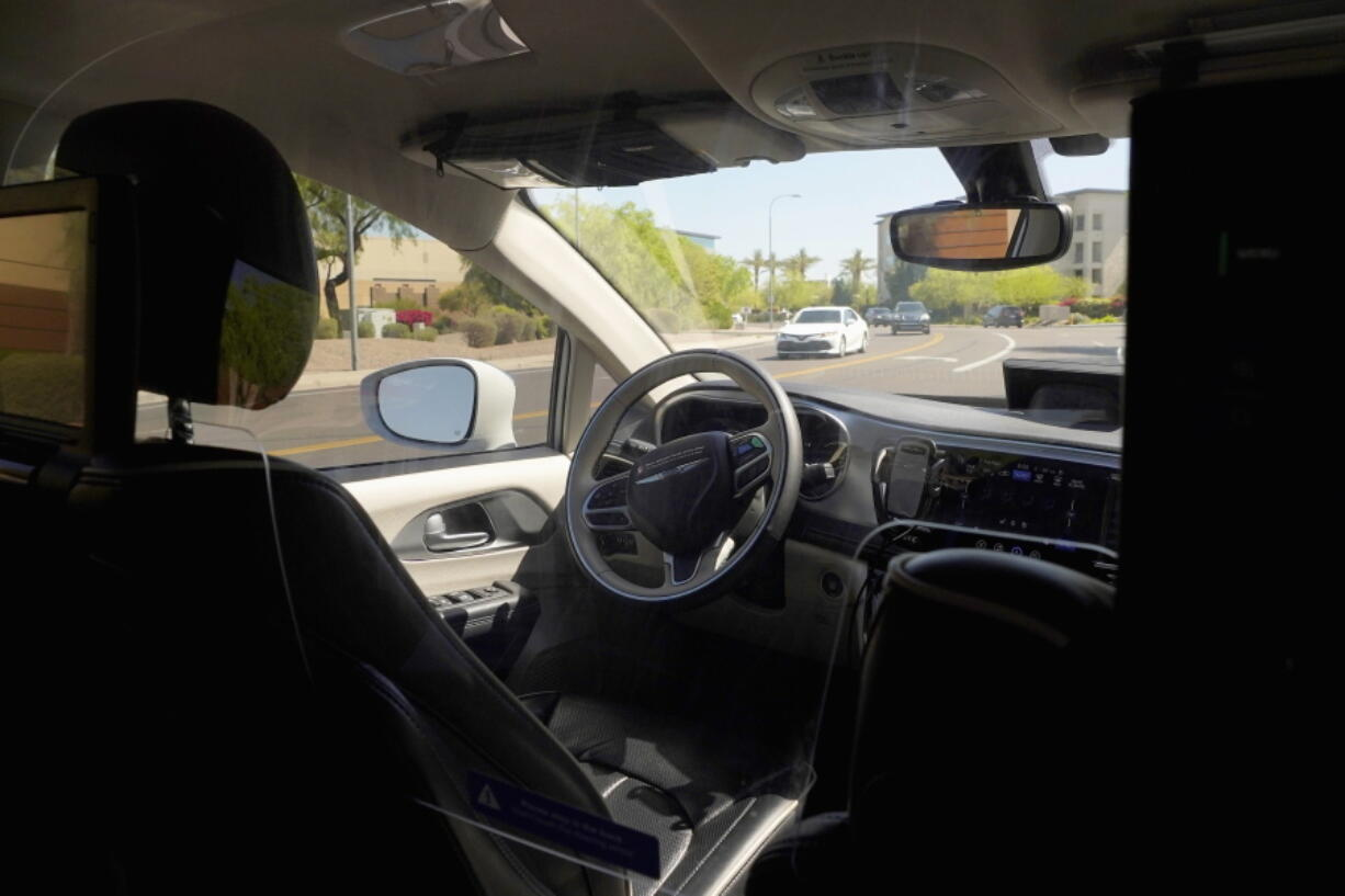 A Waymo minivan moves along a city street as an empty driver's seat and a moving steering wheel drive passengers during an autonomous vehicle ride, Wednesday, April 7, 2021, in Chandler, Ariz.  Waymo, a unit of Google parent Alphabet Inc., is one of several companies testing driverless vehicles in the U.S. But it's the first offering lifts to the public with no humans at the wheel who can take over in sticky situations. (AP Photo/Ross D. Franklin) (Ross D.