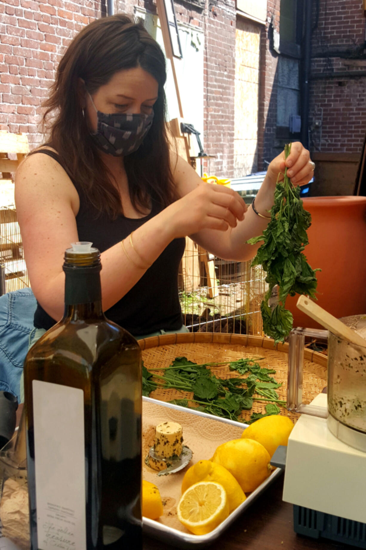 """Self-described """"folk herbalist"""" Emily Reudink teaches students how to make nettle pesto at an outdoor workshop at Kindred Homestead Supply."""