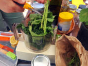 Emily Reudink puts the ingredients for nettle pesto into a food processor during a recent workshop about nettles.