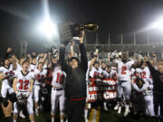 Camas head coach Jon Eagle hoists the trophy into the air after Saturday?s win in the Class 4A state championship game against Bothell at Mount Tahoma High School in Tacoma on Dec. 7, 2019.