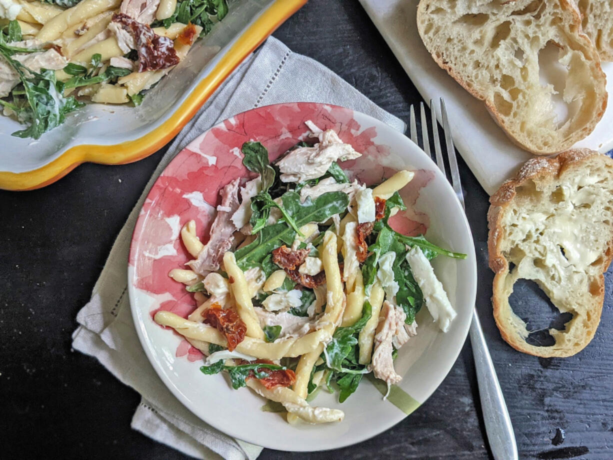 Pasta salad with dried tomatoes, arugula and shredded chicken.