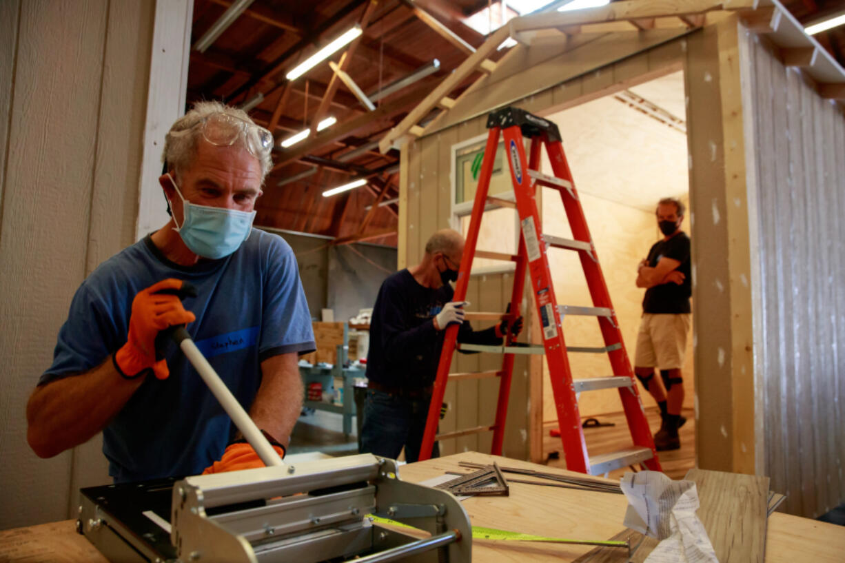 Sound Foundations NW volunteer Stephen Markowitz, left, works to install flooring in a tiny home June 3 at The Hope Factory in Seattle.