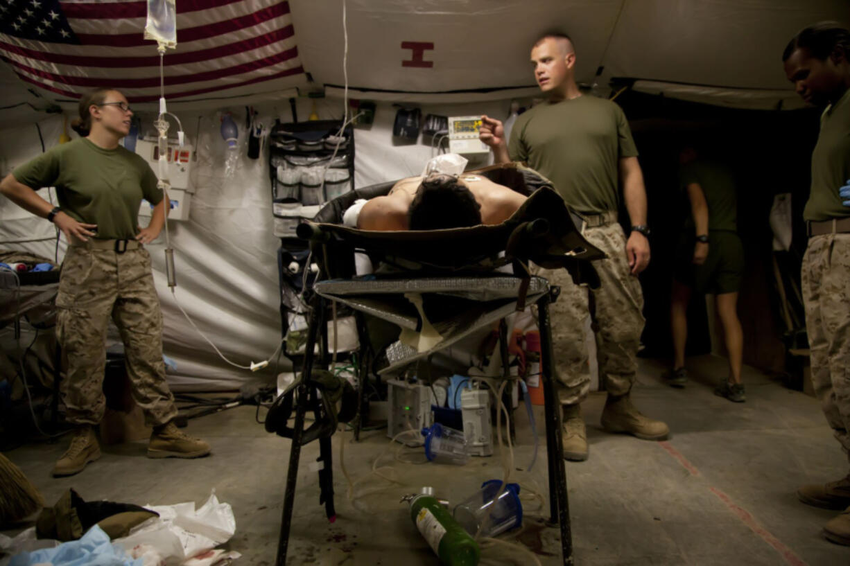 In June 2012, medical personnel at Forward Operating Base Edinburgh, in Helmand Province, discuss a patient???s case. (Nelvin C.