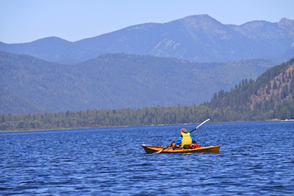 This undated photo shows a kayaker paddling across Upper Priest Lake, Idaho, to a remote campground. Idaho has doubled fees for out-of-state campers.