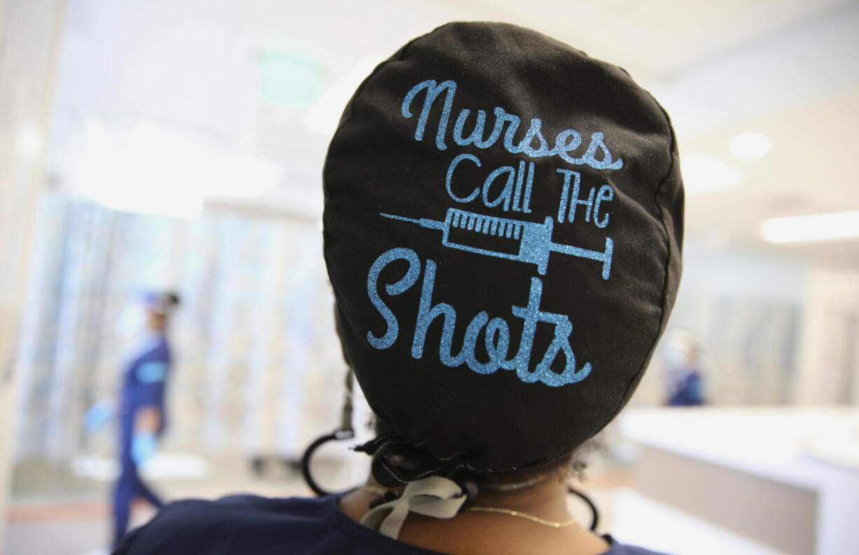 Travel nurse Tiquella Russell of Texas displays her scrub cap shortly after administering a dose of the COVID-19 vaccine at a clinic at Martin Luther King Jr. Community Hospital in South Los Angeles on Feb. 25, 2021. African Americans and Latinos comprise a majority of the South LA community and are dying of COVID-19 at a rate significantly higher than whites. Vaccine equity has also lagged in South Los Angeles relative to some more wealthy areas.