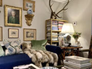 The brass and glass coffee table holds favorite books while allowing the leopard rug to make its presence known in Jim Miller's chic and charming home. Scottish roebuck antlers draw the eye up and add height.
