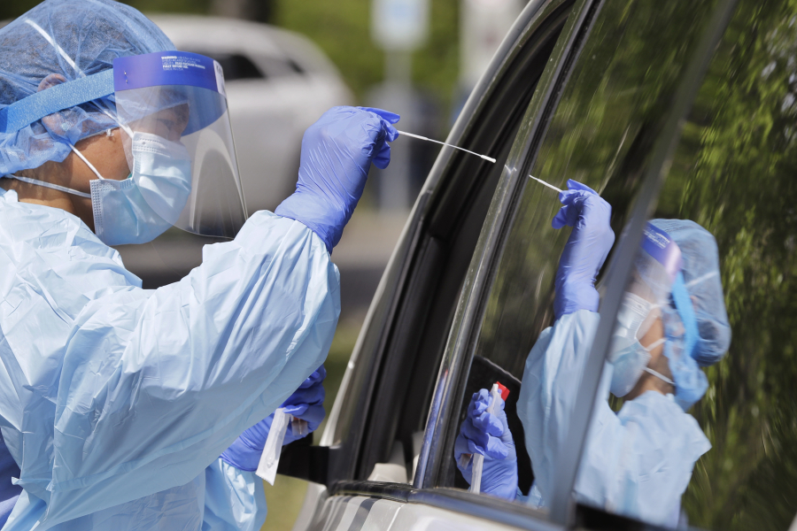 Medical assistant Melanie Zamudio is reflected in the window of a car as she reaches in to take a nasal swab from a driver at a drive-up coronavirus testing site in April 2020 in Seattle.