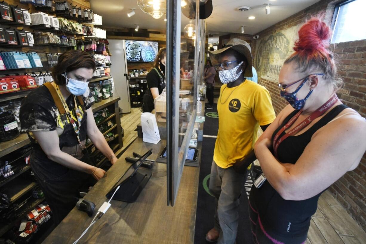 Budtender Kelley Dearing helps customers Timothy Benison and Sharon Stricklan with their purchases at the Greenhouse, a recreational and medical marijuana dispensary, in Walled Lake, Michigan on June 7, 2021.