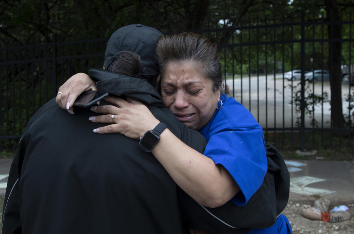 Brenda Ramos, left, comforts Elizabeth Gonzales at the location where her son was killed by an Austin police officer on April 22, 2021. The memorial for Alex Gonzales Jr. has been removed from Wickersham Lane four times and Elizabeth Gonzales doesn't know why or who is doing it. Ramos' son, Michael, was killed a few blocks away, also by an officer. The mothers take turns checking on their son's memorial.