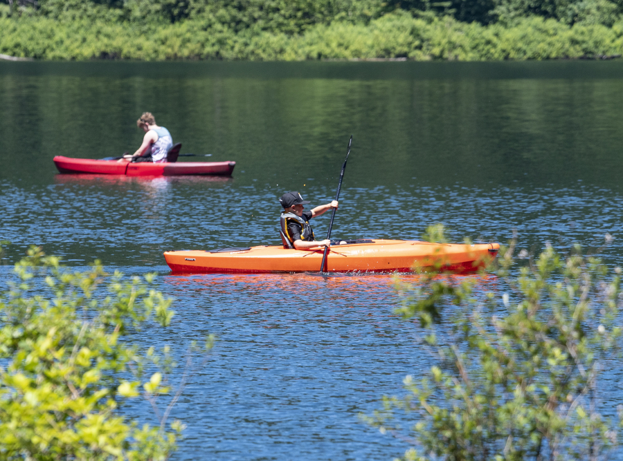 Kayakers paddle on the water Saturday at Battle Ground Lake State Park.