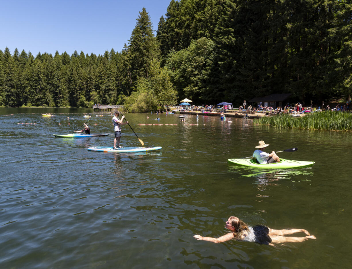 Swimmers, kayakers and stand-up paddleboarders enjoy an afternoon on the water Saturday at Battle Ground Lake State Park.
